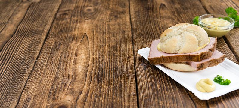 Portion of German Leberkaese on wooden background (selective foc