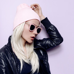Stylish blonde in fashionable hat beanie and pink glasses Vanill