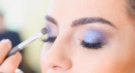 Girl doing make-up in a beauty salon.Focus on near eye. Shallow depth of field