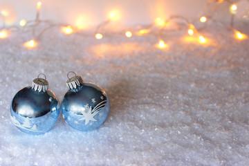 Zwei blaue Christbaumkugeln im Schnee mit Lichteffekten im Hintergrund