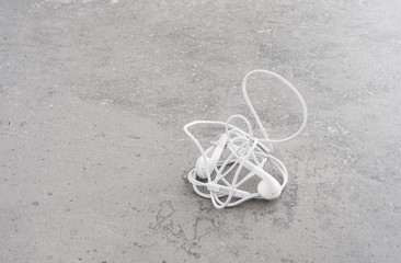 White headphones with tangled wire lying on stone table. Concept of audio, sound or mobile accessory.