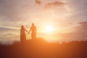 a silhouette of a man and woman holding hands with each other, w