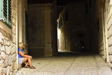 Women sitting in a dark alleyWomen sitting in a dark alley, picture from Postira city on Brac Island in Croatia.