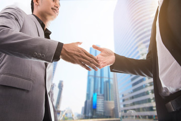 handshake on a city background. business, partnership, cooperation and gesture concept -two businessman shaking hands over city background.