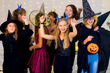 Happy group of teenagers dance in Halloween costumes