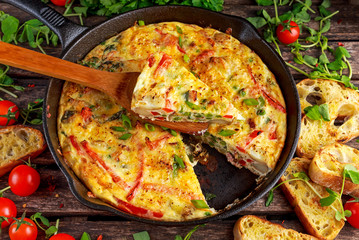 Wall Murals Ready meals Frittata made of eggs, potato, bacon, paprika, parsley, green peas, onion, cheese in iron pan. on wooden table.