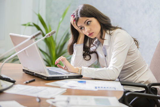 young woman businessman works behind laptop
