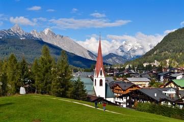 Aussicht über die Hausdächer der Gemeinde Seefeld, der Olympiaregion im Tirol, mit Blick auf die Kirche und die Tiroler Berge, Österreich