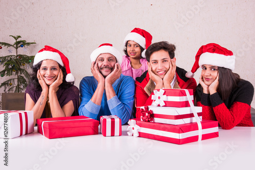 christmas time, Happy indian family sitting across table with hands