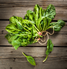 Bunch of fresh raw spinach on a rustic wooden table, top view