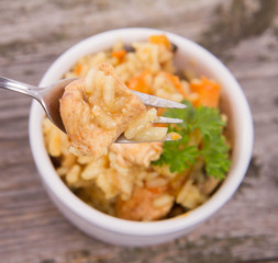 Risotto with chicken, bell pepper, onion, portobello and parsley on a wooden background