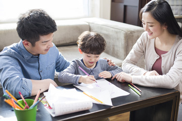 Young parents helping son with homework