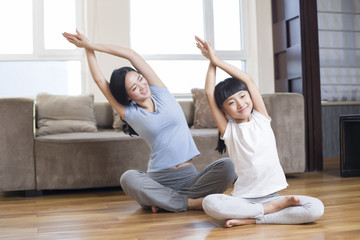 Smiling mother and daughter doing yoga at home