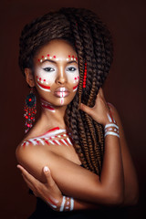 African style woman . Attractive young woman in ethnic jewelry. close up portrait. Portrait of a woman with a painted face. Creative makeup and bright style.
