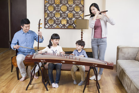 Young family playing traditional musical instruments at home