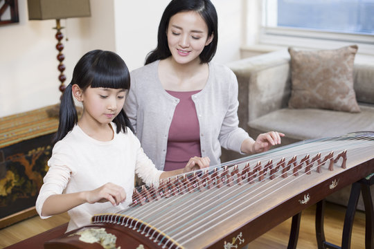 Mother teaching traditional musical instrument zither