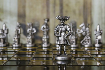 Metal chess. Beautiful and unusual chess pieces. Vintage background.