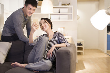 Young couple using smart phone on living room sofa