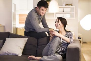 Young couple using smart phone on living room sofa