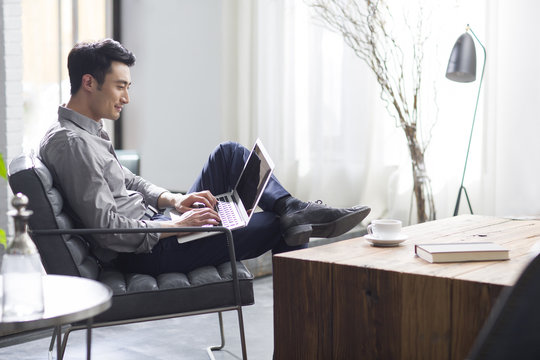 Young man working with laptop in office
