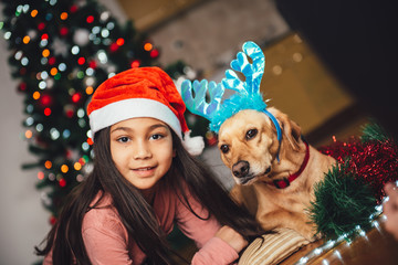Girl with santa hat and dog laying down by the christmas tree