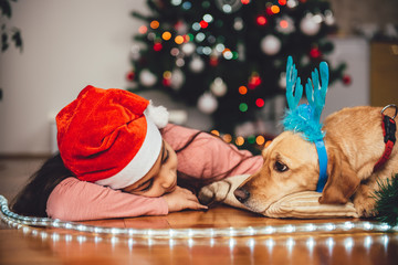Girl and dog laying down by the christmas tree