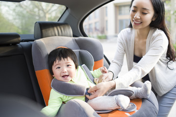 Mother fastening seat belt for daughter