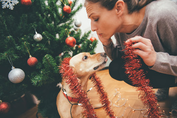 Woman decorating a christmas tree and cuddling a dog