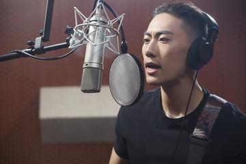 Young man singing in recording studio