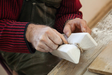 fine hand sanding a piece of marble with sandpaper