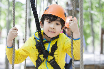 Little boy playing in tree top adventure park