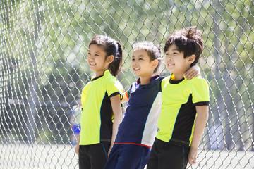 Happy children in sportswear leaning against chainlink fence