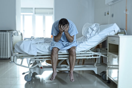 desperate man sitting at hospital bed alone sad and devastated s