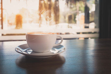 Cup of hot coffee on table in cafe with morning light , vintage or retro color toned.
