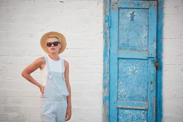 Pretty slim tan blonde stylish woman in straw hat and sunglasses posing