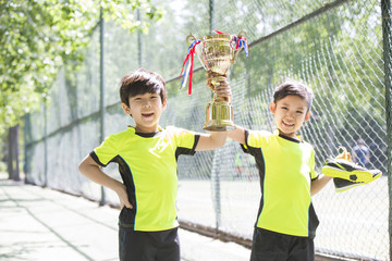 Happy children in sportswear showing their trophy