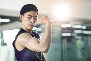Young man in sports clothing flexing his muscles