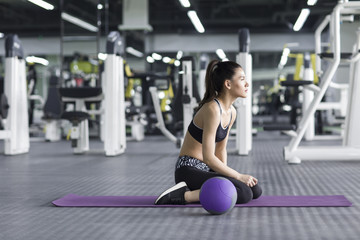 Young woman sitting on yoga mat with exercise ball in gym