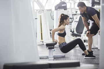 Young woman working out with trainer in gym