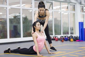 Yoga instructor helping young woman with pose