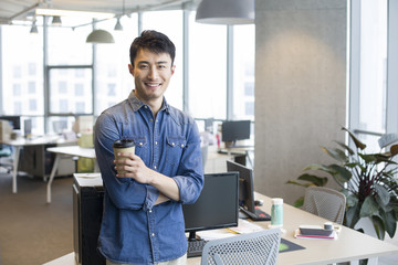 Portrait of young businessman holding coffee cup in office