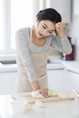 Young woman kneading dough on cutting board