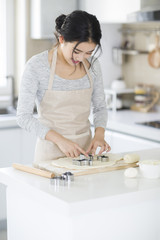 A smiling young woman making cookies in the kitchen
