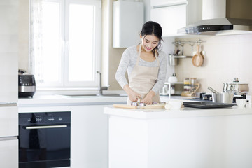 Smiling young woman making cookies in the kitchen