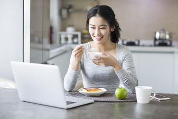 Young woman having a breakfast while looking at laptop