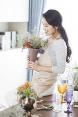 Young woman arranging flowers at home