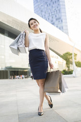 Young woman with shopping bags walking on street