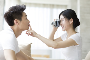 Young couple taking photos at home