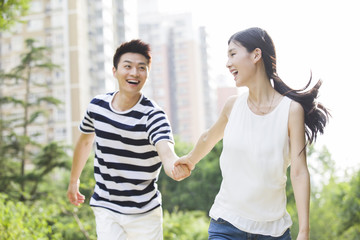 Happy young couple holding hands outdoors