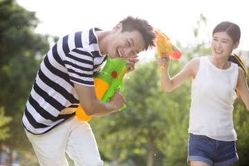 Happy young couple playing squirt guns